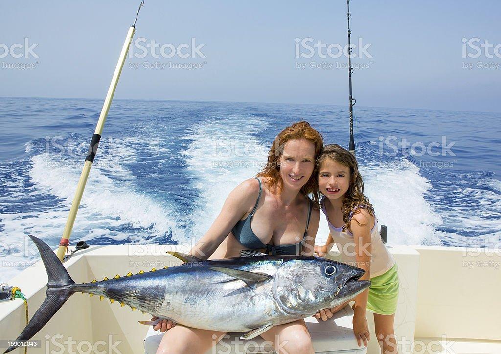 bikini fisher woman and daughter with bluefin tuna stock photo