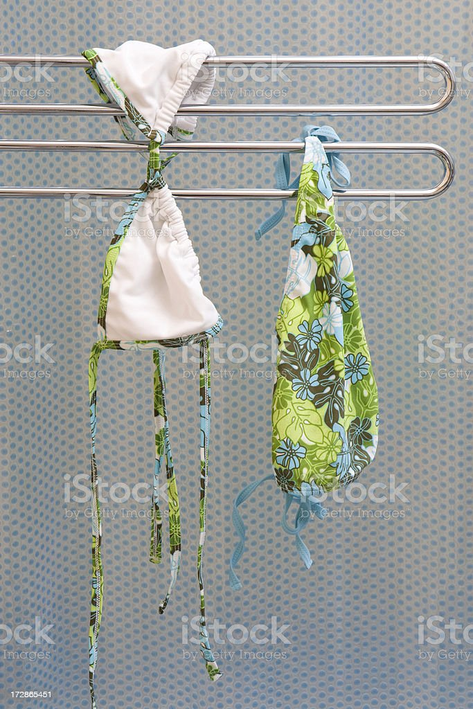 A bikini hanging on a metal rod to dry out indoors. royalty-free stock photo