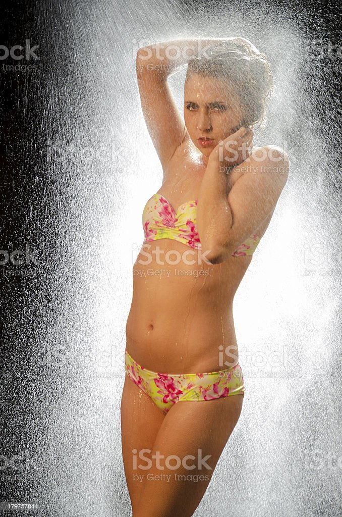 Bikini model in white water spray, looking at camera. royalty-free stock photo