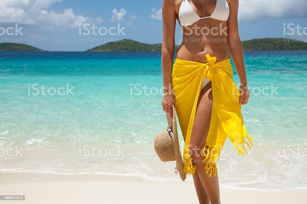 bikini woman in yellow sarong holding hat at a beach stock photo