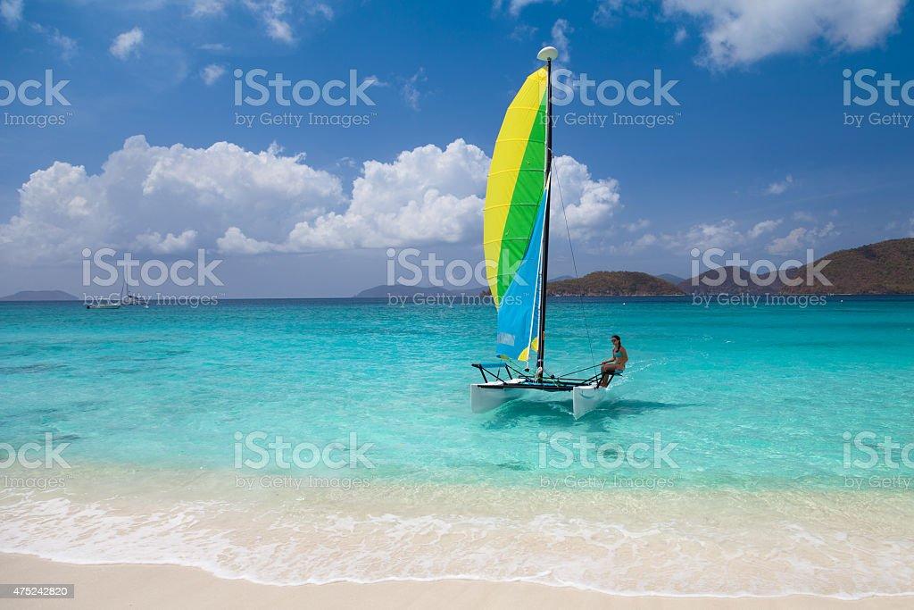 bikini woman sailing on a catamaran toward the Caribbean beach stock photo