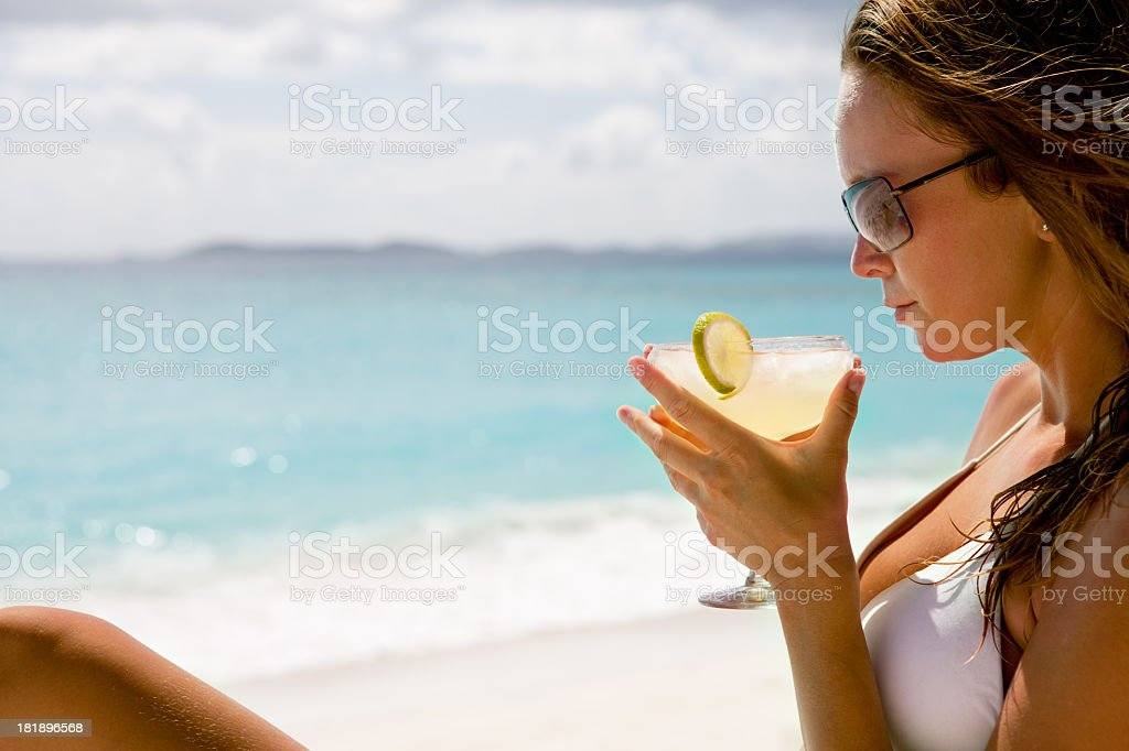 bikini woman sunbathing at the beach with margarita cocktail stock photo