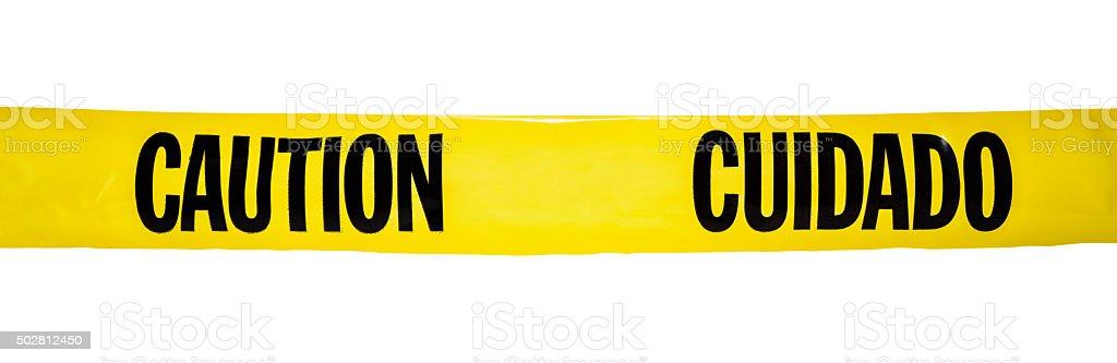 Bilingual yellow CAUTION / CUIDADO tape on white background stock photo