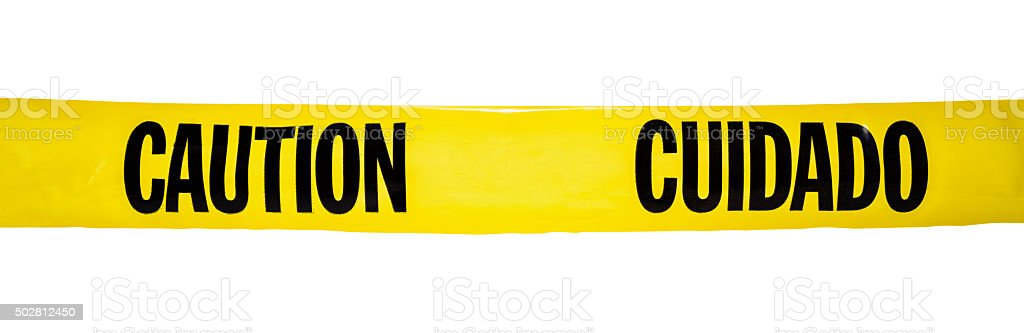 Bilingual yellow CAUTION / CUIDADO tape on white background stock photo