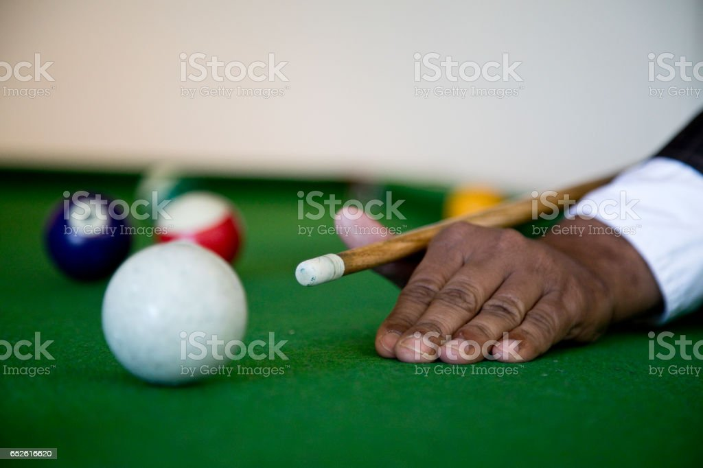 Billiards player striking the ball stock photo