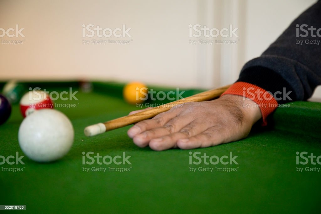 Billiards player striking the ball stock photo