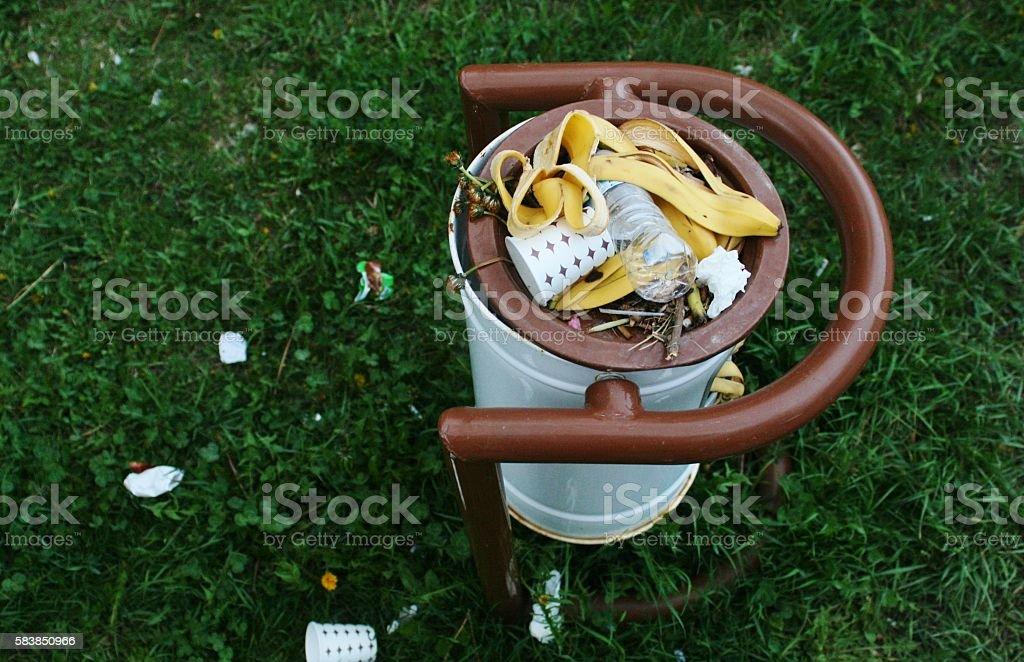 bin-full of trash on the green stock photo