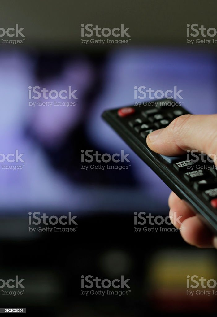 A hand with remote control and TV in the background