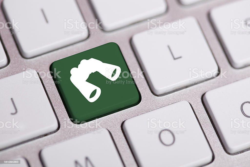 Binocular Icon on Keyboard-Searching Concept stock photo