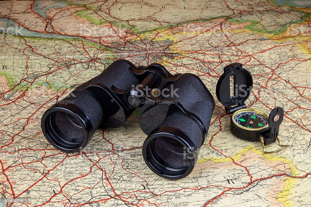Binoculars and Compass on Old Route Map stock photo