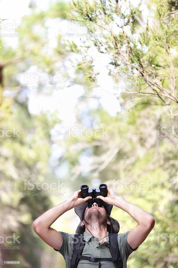 Binoculars - man hiker looking up stock photo