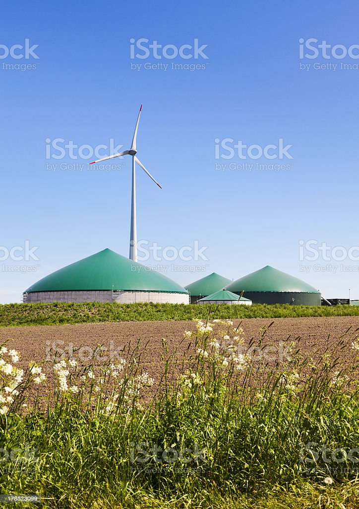 Biogas plant and wind turbine stock photo