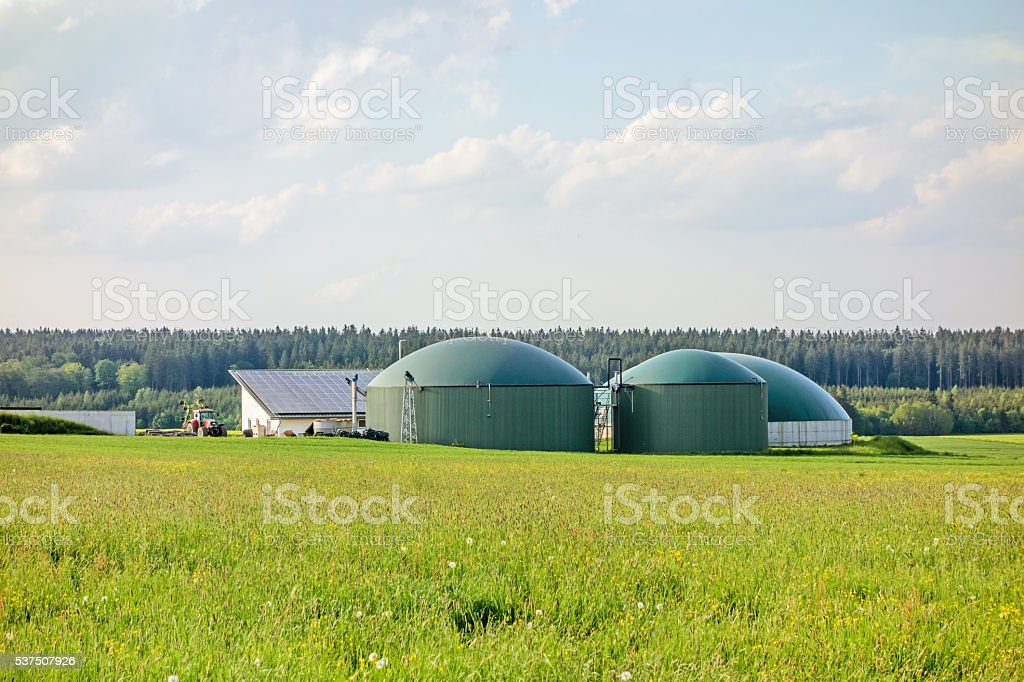 Biogas plant on green meadow stock photo