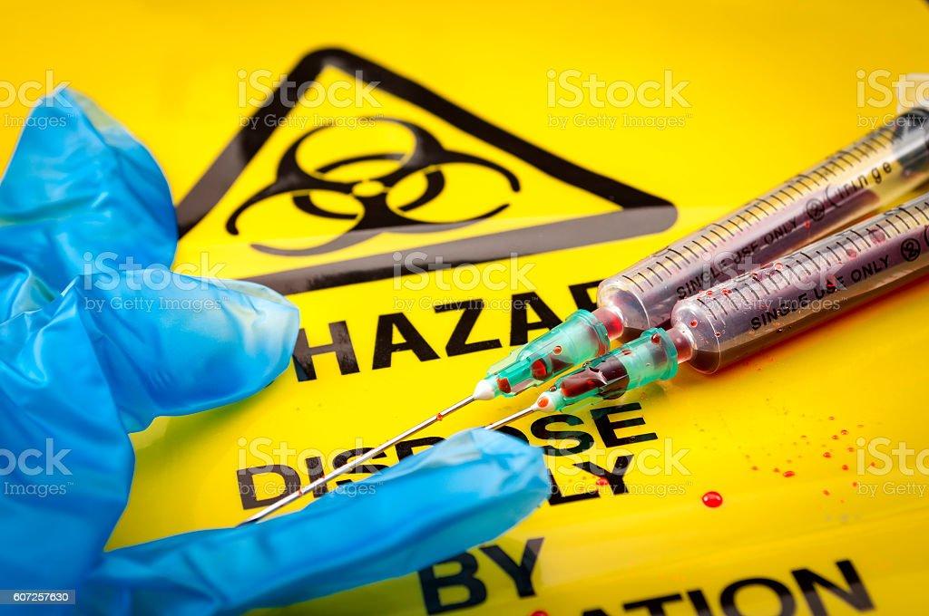 Biohazard logo, medical gloves and syringes stock photo