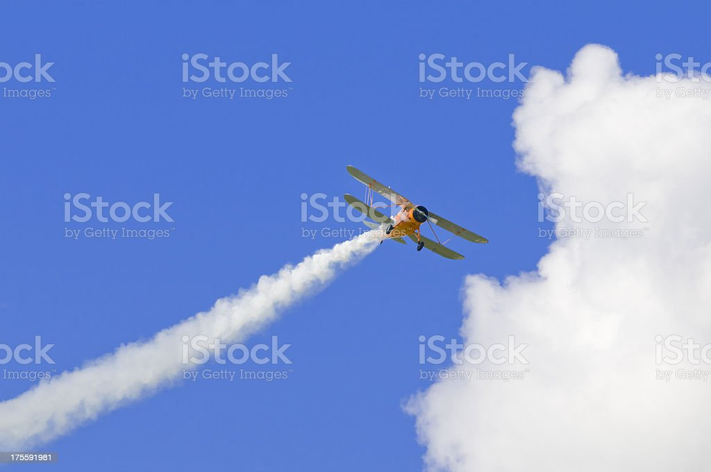 Biplane with a vapour trail, blue sky and cloud stock photo