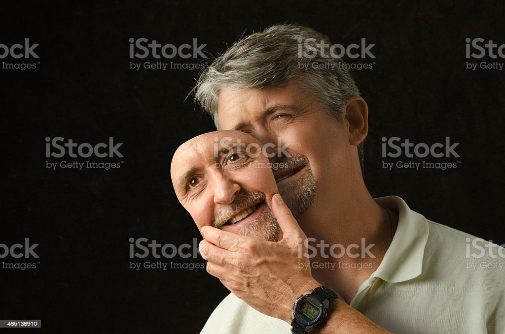 Bipolar disorder depressed man removing his mask of happiness stock photo