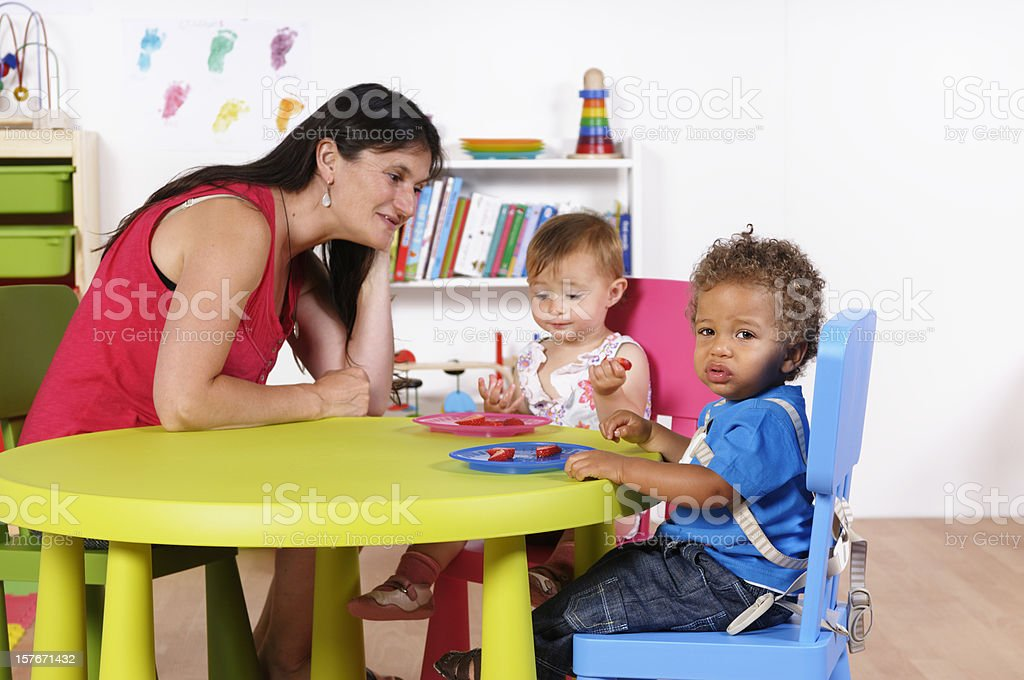 Biracial Baby Boy Looks Away While Carer Watches Peer royalty-free stock photo