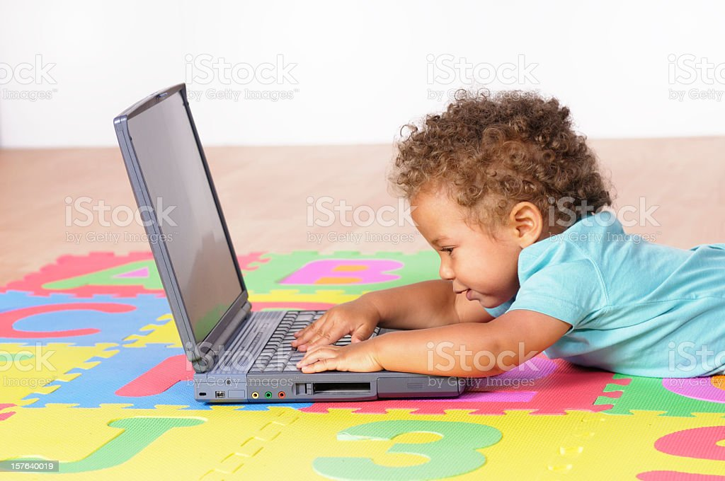 Biracial Baby Boy Lying Down And Using A Laptop stock photo