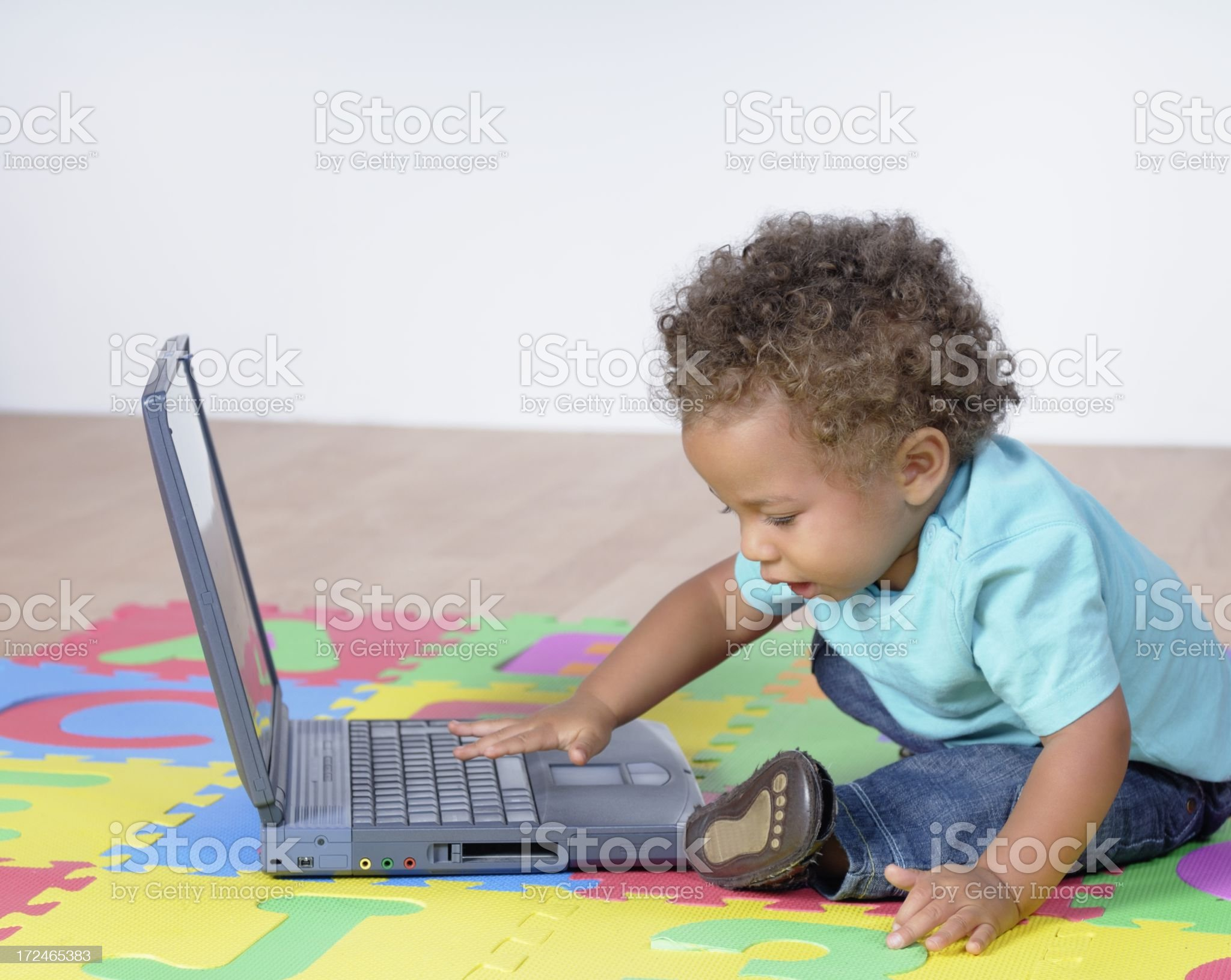 Biracial Baby Boy/ Toddler Using A Laptop On The Playmat royalty-free stock photo