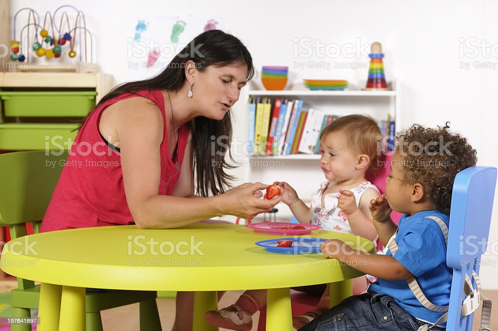 Biracial Baby Boy Watches As His Peer Is given Fruit stock photo