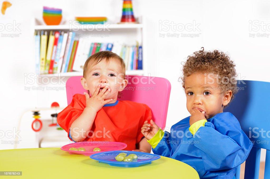 Biracial Baby Boy/Toddler And Peer Eating Fresh Fruit stock photo