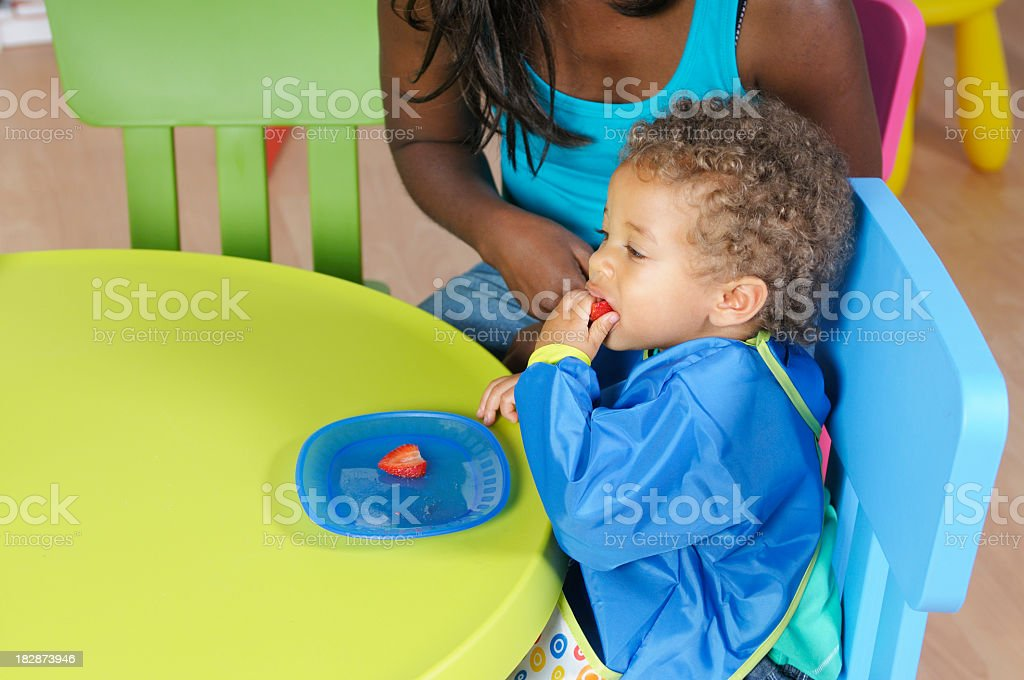 Biracial Baby/Toddler Eating A Strawberry stock photo