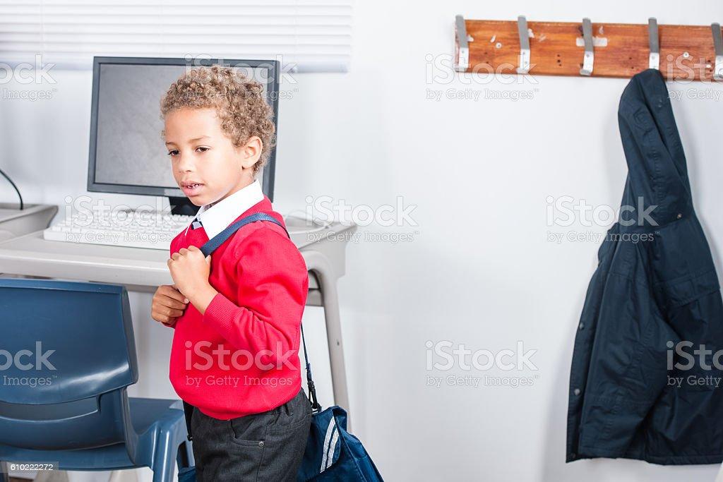 Biracial Boy Walking to Class after Hanging up his Coat stock photo