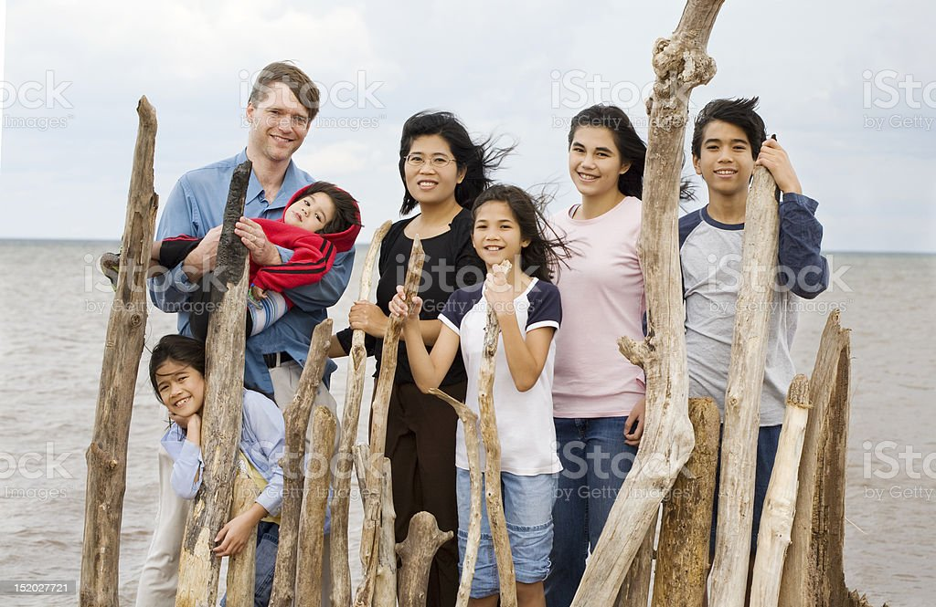 Biracial family together at the beach in summer stock photo