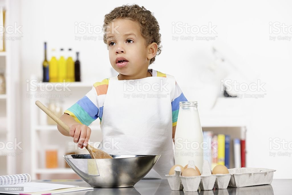 Biracial Little Boy Contemplating While Preparing Food royalty-free stock photo