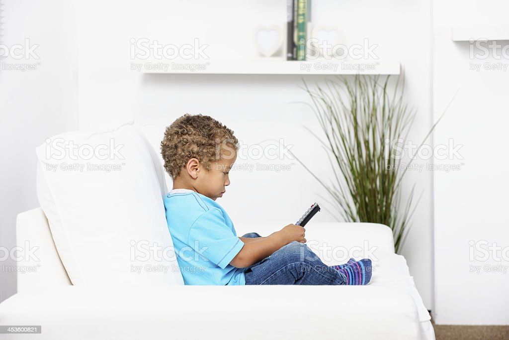 Biracial Little Boy Fiddling With A Remote Control stock photo