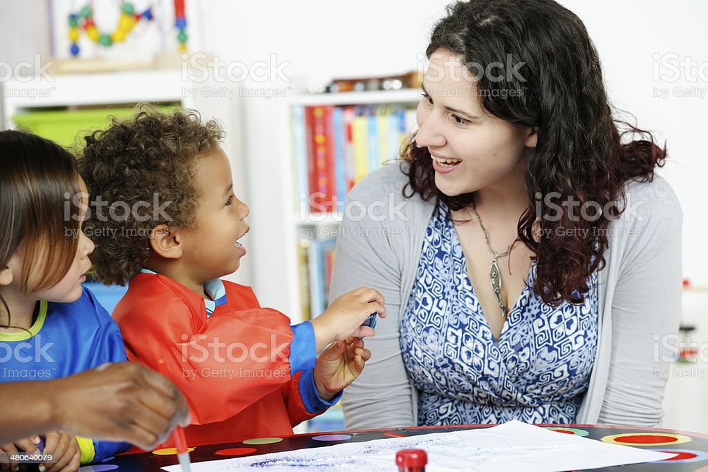 Biracial Little Boy Interacting With Carer/ Teacher stock photo