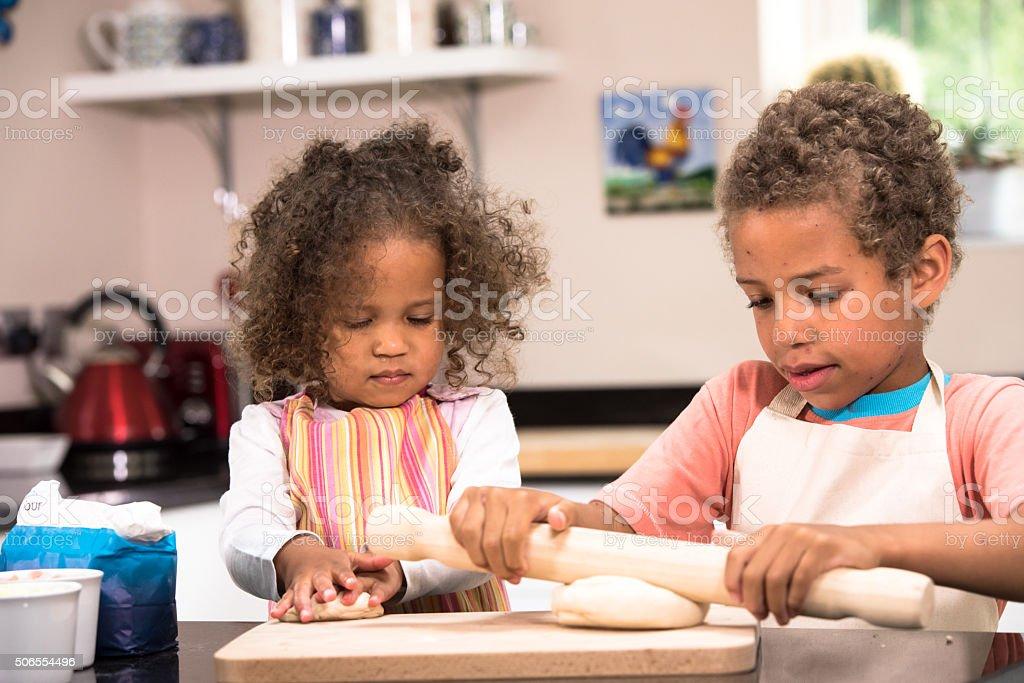Biracial Little Girl And Boy Preparing Dough stock photo