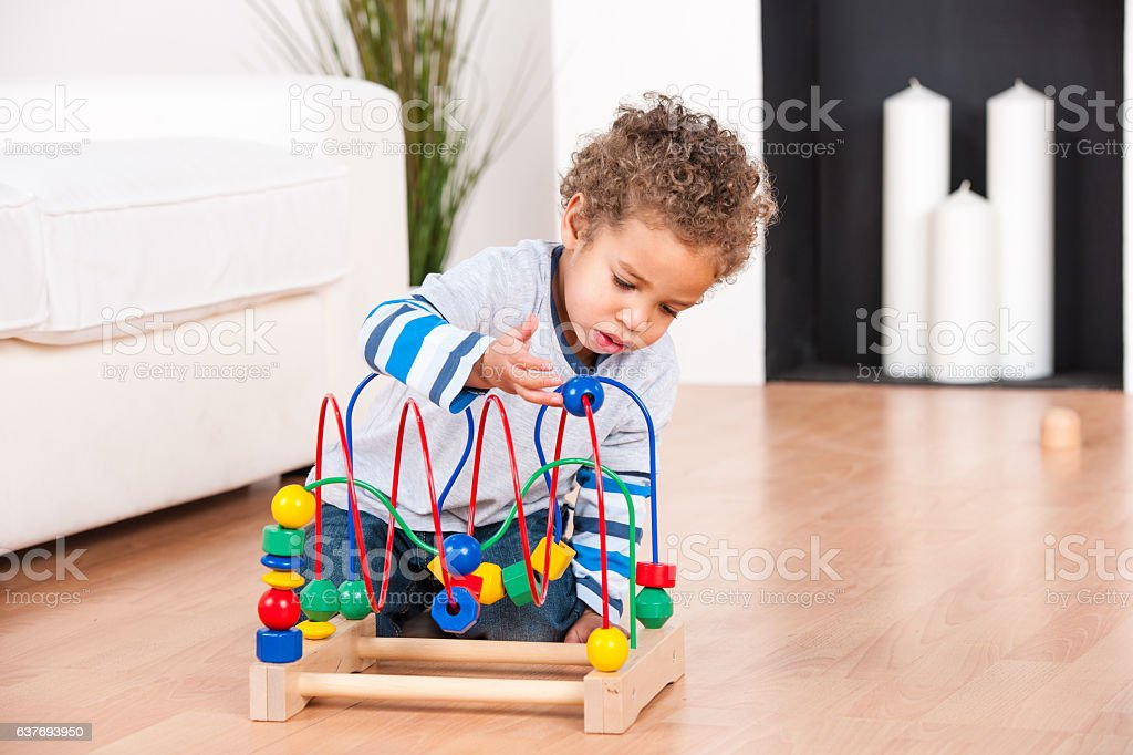 Biracial Little Playing Independently In The Living Room stock photo