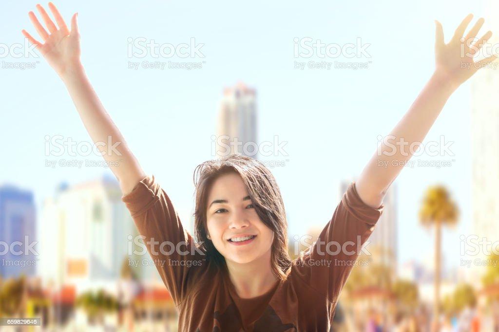 Biracial teen girl arms raised, urban background stock photo