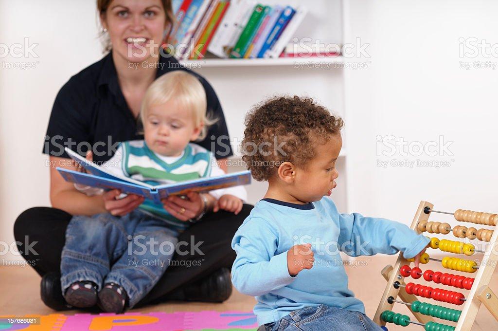Biracial Toddler Playing While His Peer Enjoys Storytime royalty-free stock photo