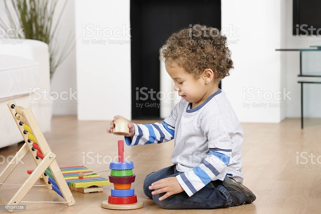 BiracialToddler/ Little Boy Playing With Rings In The Living Room stock photo