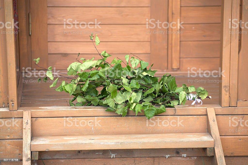 Birch broom lying on wooden porch of rural village bath stock photo