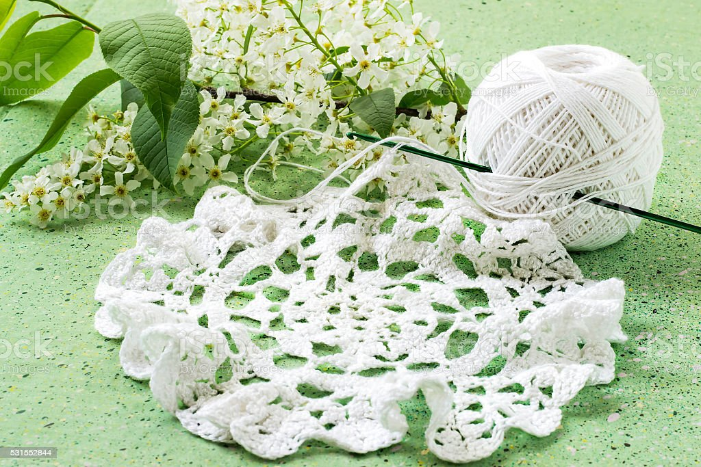Bird cherry and knitted lace doily stock photo