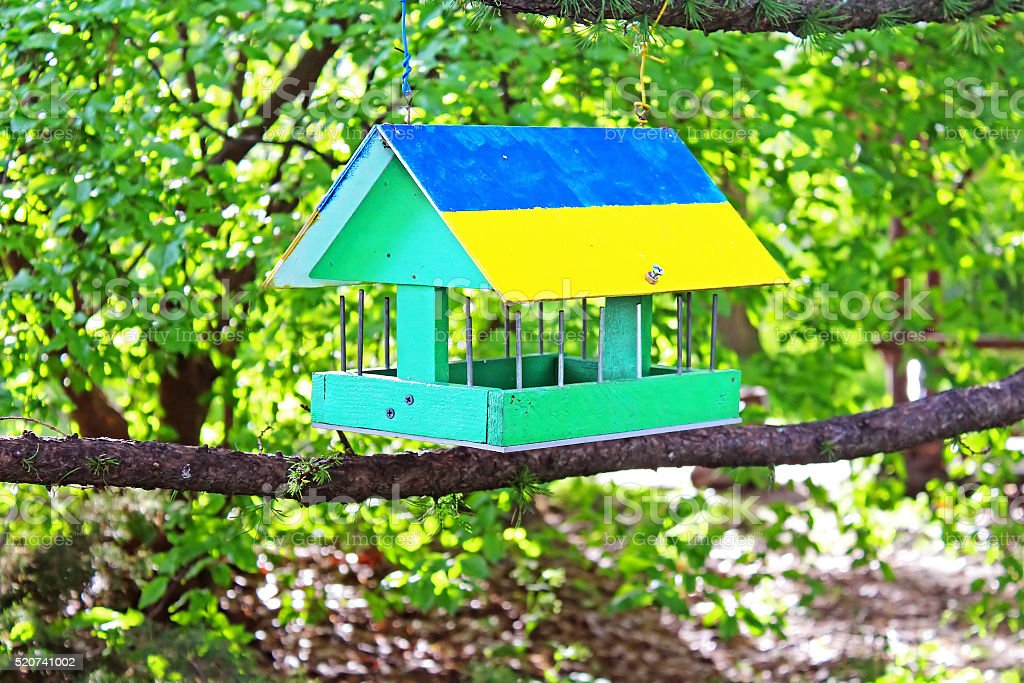 Bird feeder painted as Ukrainian flag in the summer forest stock photo