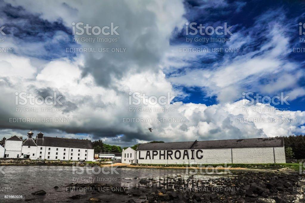 A bird flies across a dramatic sky set over the Laphroaig Distillery stock photo