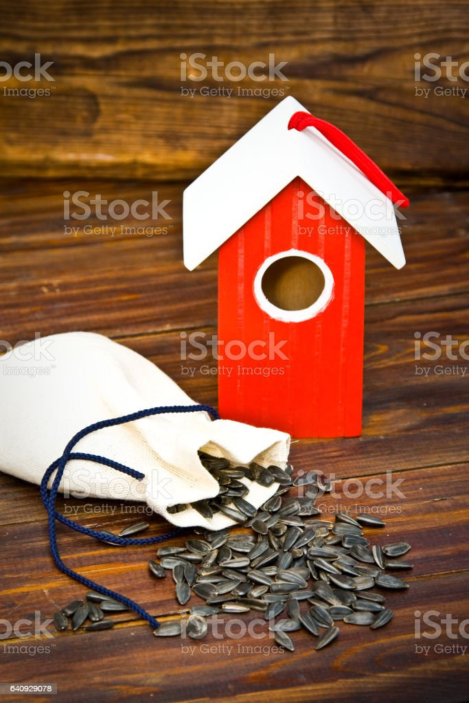 Bird house and seeds on wood stock photo