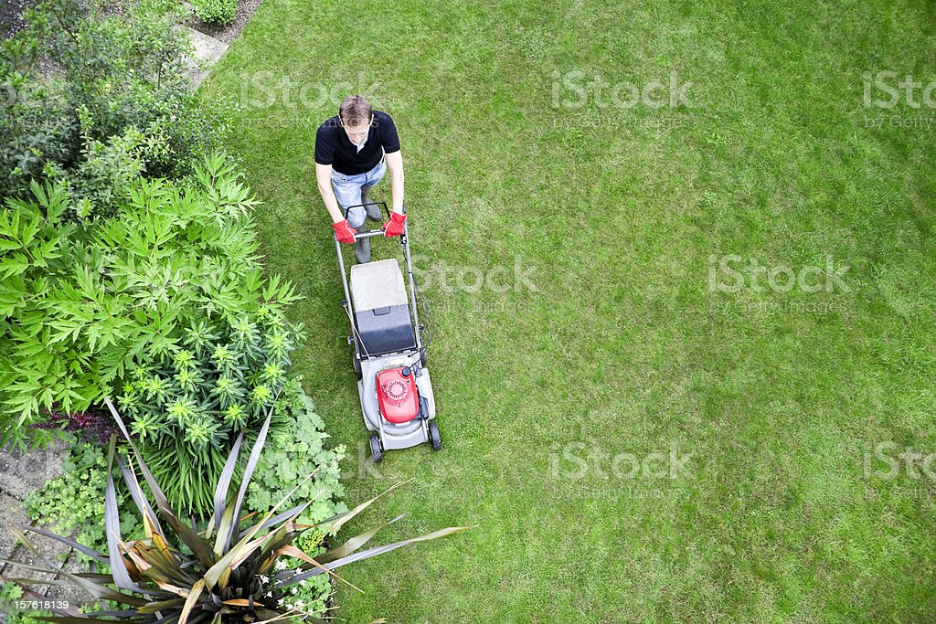 Bird's Eye View of Gardener Mowing Lawn stock photo