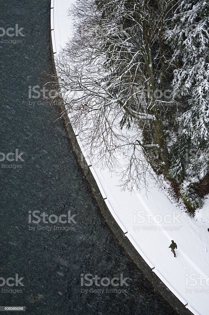 Birds eye view of man walking in the winter snow stock photo
