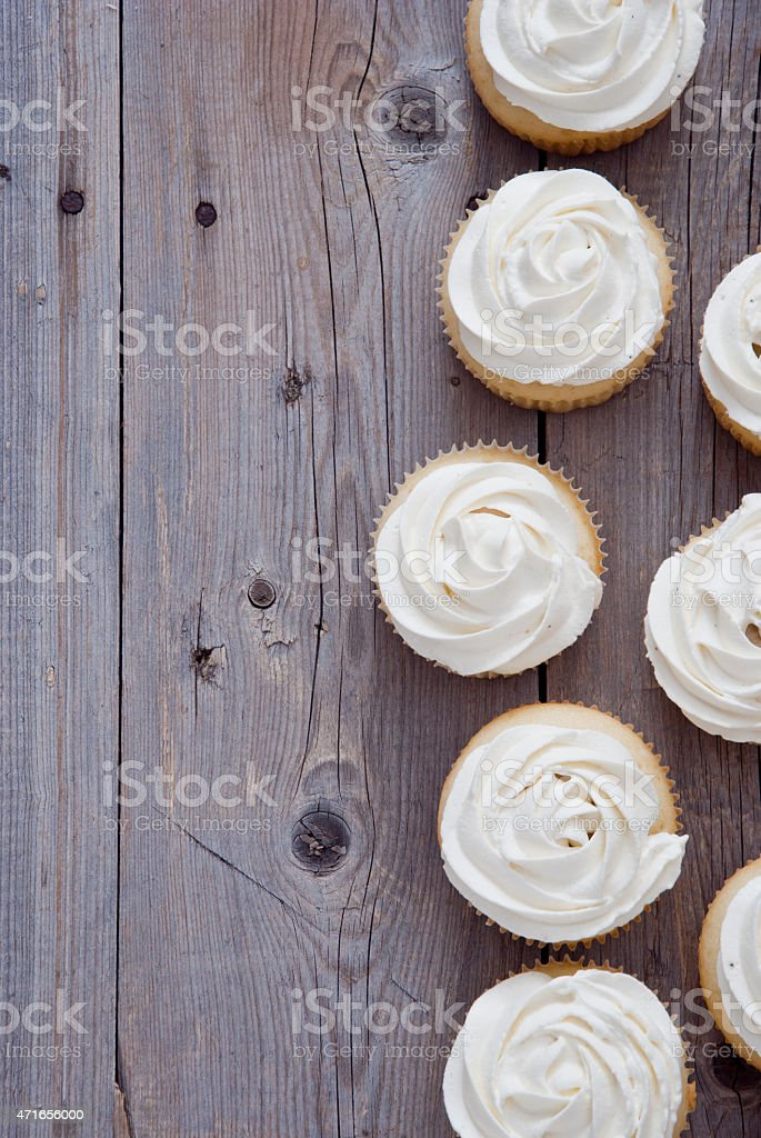 Birds eye view of vanilla cupcakes on wooden counter stock photo