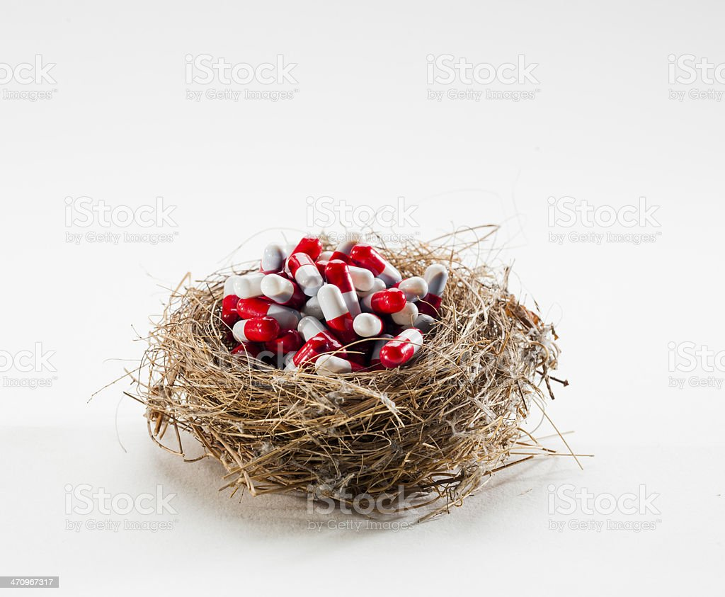 Birds' nest full of pills and medication on a white background. royalty-free stock photo