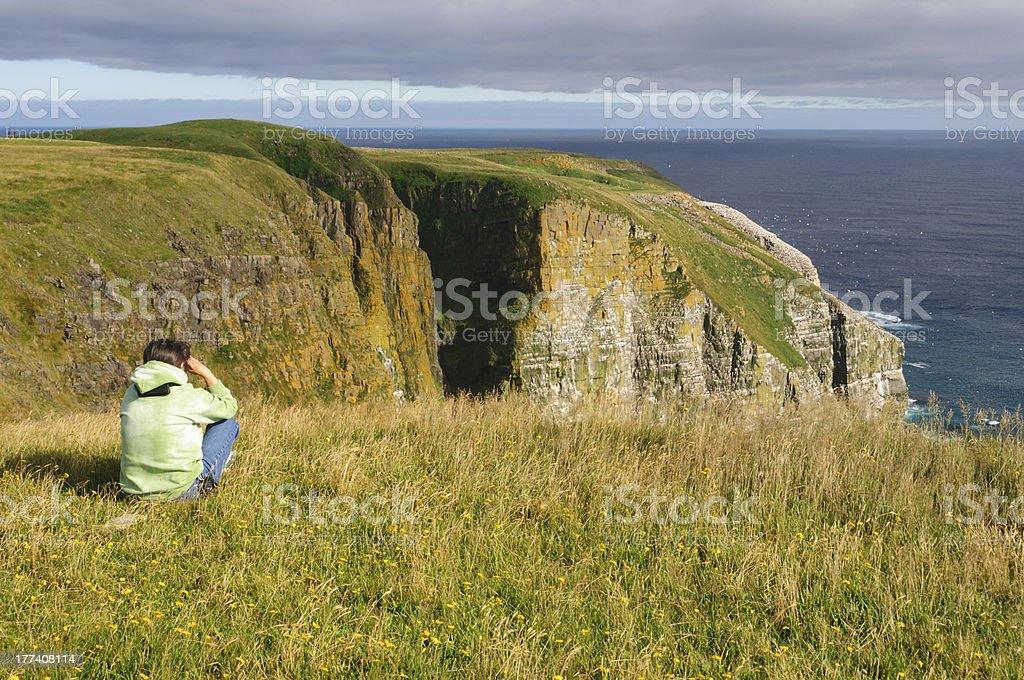 Birdwatcher looking at birds on Coastal Cliffs stock photo