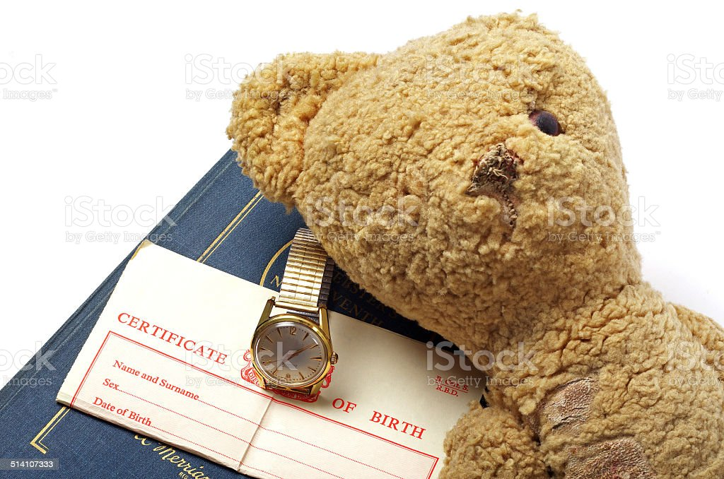 birth certificate with book and teddy bear stock photo