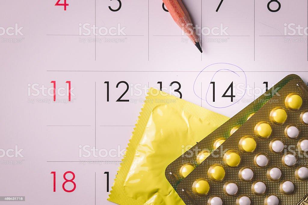 Birth control pills on calendar stock photo