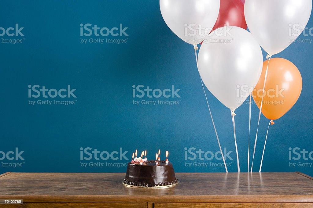Birthday cake and balloons stock photo