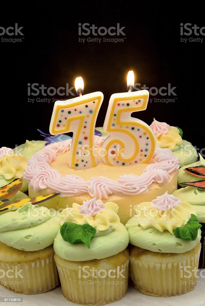birthday cake surrounded by cupcakes with a seventy five candle royalty-free stock photo